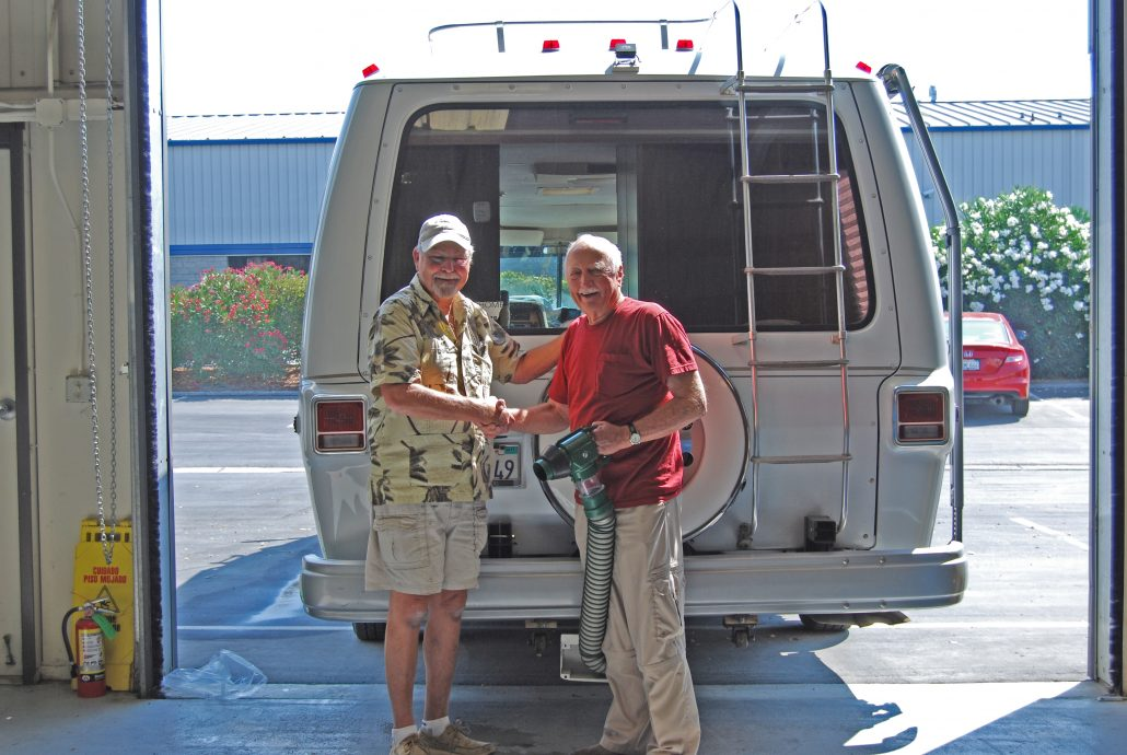 Shaking hands after custom install for RV Waste System